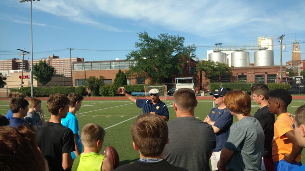 Coach Nick Restifo demonstrates passing grip to young quarterbacks.