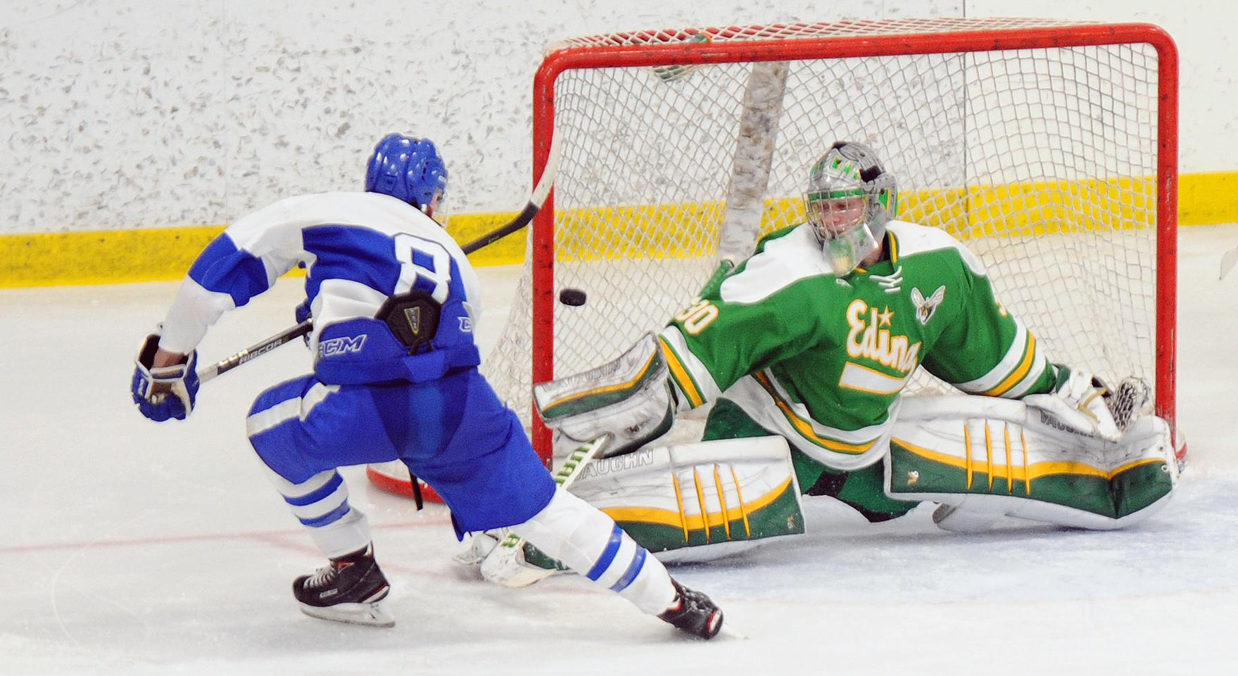 Minnetonka's Luke Loheit fires a shot past Edina's Garrett Mackay in the third period on Saturday afternoon as the No. 2 Skippers beat No. 1 Edina 5-3. Photo by Loren Nelson, legacyhockeyphotography.net
