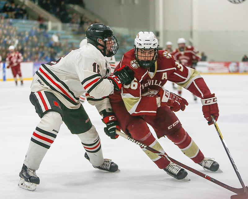 Lakeville North's Garrett Daly (left) slowed Lakeville South's Zachary Bauer in the second period. Bauer's third-period goal pulled South within 4-3 with less than two minutes to play. Photo by Mark Hvidsten, SportsEngine