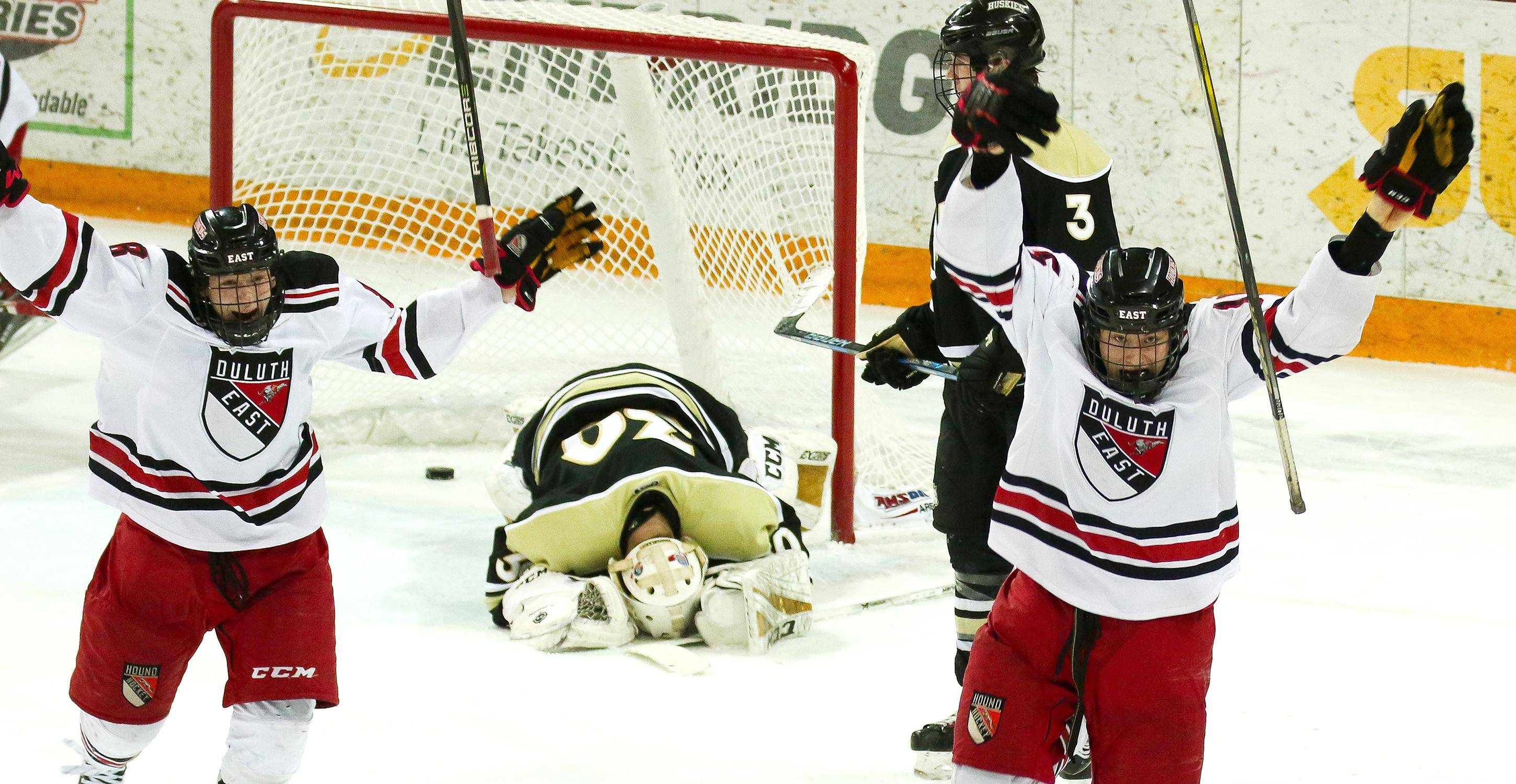 Duluth East's Ricky Lyle (right) and Austin Jouppi celebrate the Greyhounds' overtime game-winning goal Thursday in the Class 2A, Section 7 championship game against Andover. The Greyhounds won 3-2. Photo by Dave Harwig, Viewthroughmylens.net