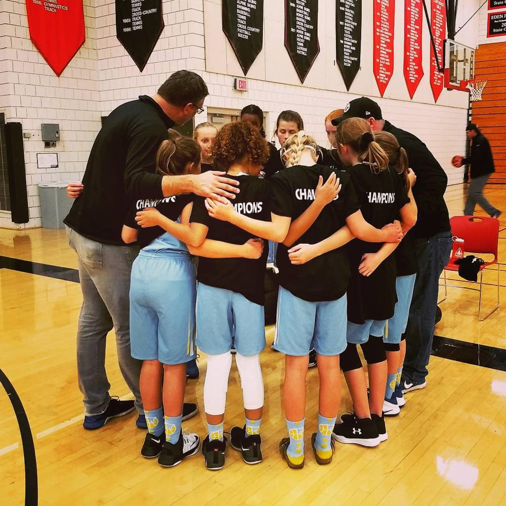 Girls 7th Grade Gold huddle up after winning the Championship game, beating the STARS 39-22