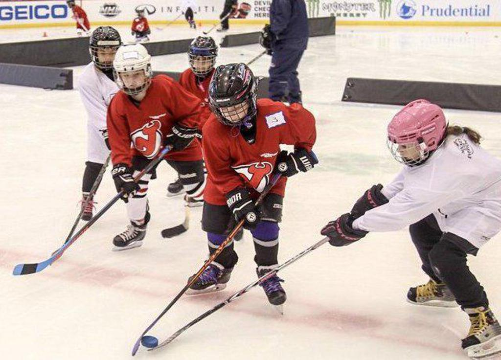 Girls hockey players battling for the puck during a clinic