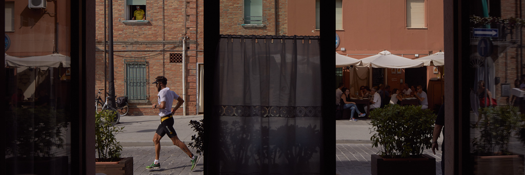 Athlete is running through the heart of Cervia seen through a store at IRONMAN 70.3 Italy Emilia-Romagna