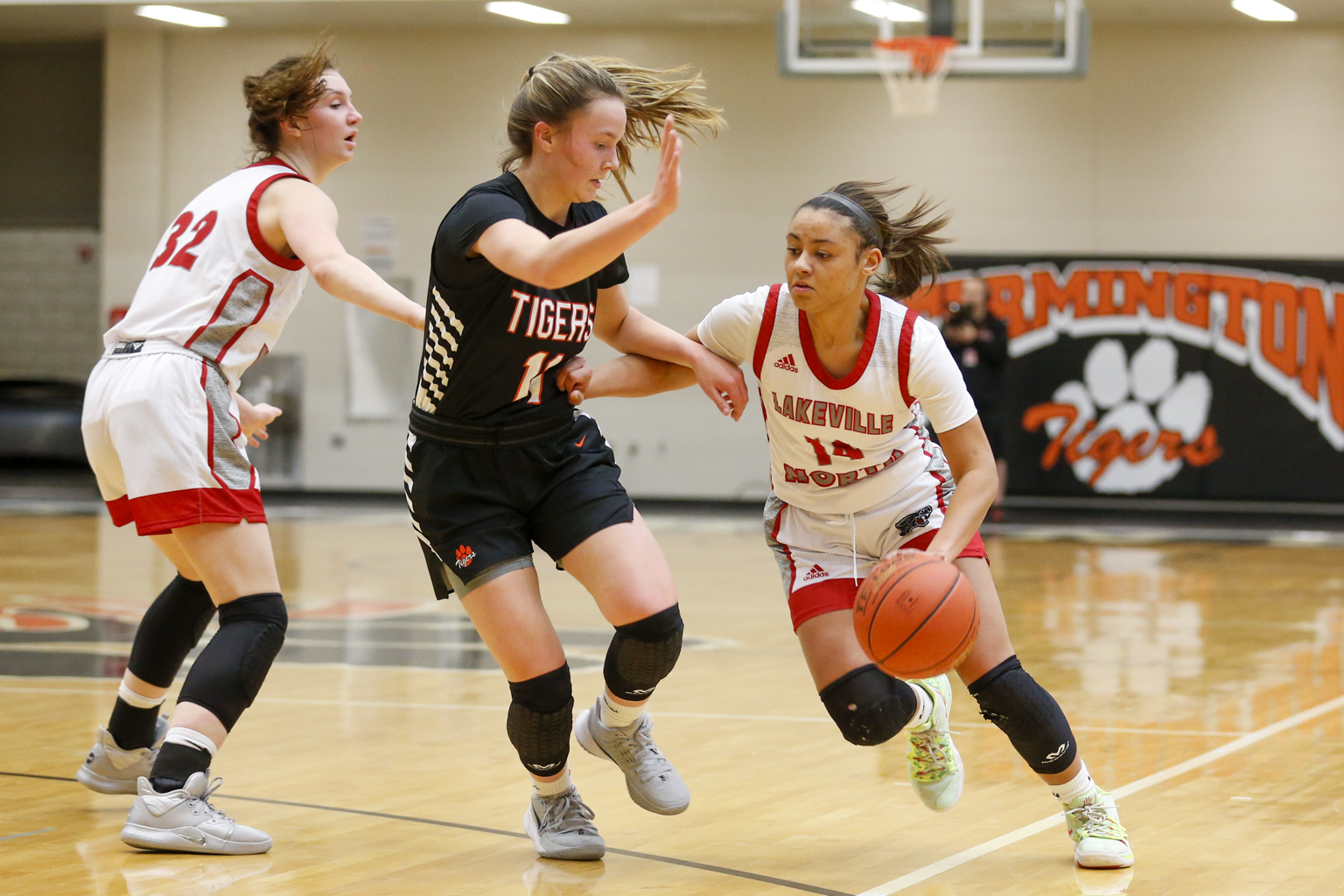 Lakeville North's Sarah Kuma (14) tries to create space to drive toward the basket as Farmington's Peyton Blandin (11) defends Tuesday night. The Panthers fell to the Tigers 64-44 in Farmington. Photo by Jeff Lawler, SportsEngine