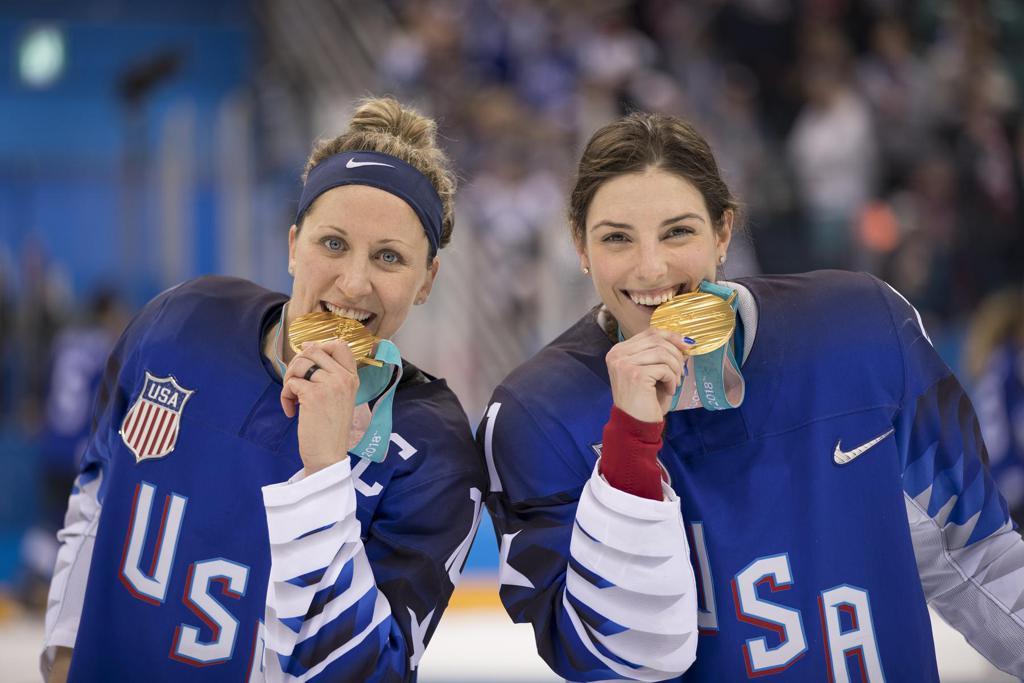 Meghan Duggan and Hilary Knight biting gold medal.