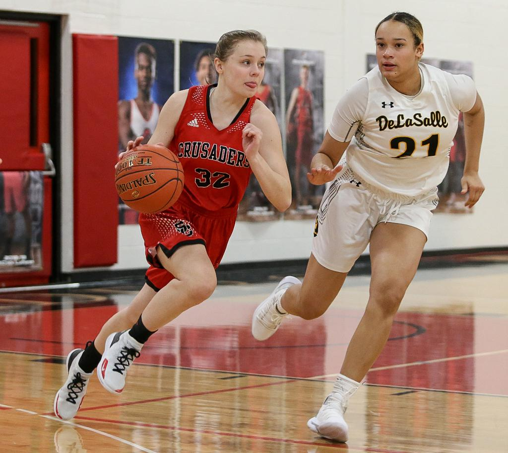 Sophomore guard Kenna Moon (32) carries the ball up court past defender Nora Francois (21). Moon scored a team-high 19 points for St. Croix Lutheran. Photo by Cheryl Myers, SportsEngine