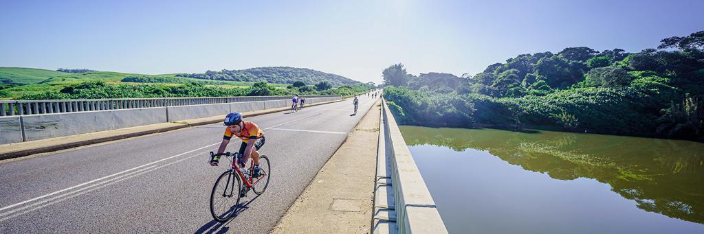 IRONMAN 70.3 Durban athletes are biking on a fast and undulating course across a bridge with green hills on the left and right side