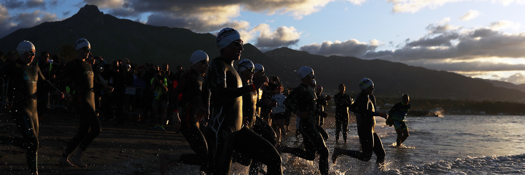 IRONMAN 70.3 Marbella athletes are about to run into the Mediterranean sea for the swim at sunrise
