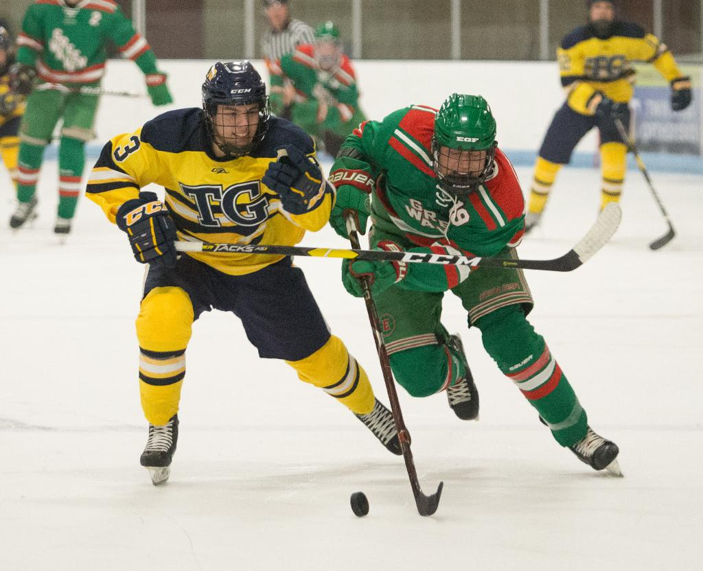 Adam Johnson (3) and Tanner Mack (19) race to the puck crossing the blue line. Mack opened up the second period with three goals in under five minutes helping the Green Wave cruise to a 7-2 win over the Eagles. Photo by Cheryl Myers, SportsEngine