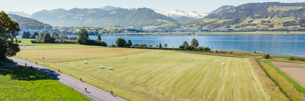 IRONMAN 70.3 Switzerland athletes biking into the majestic hills right next to the Obersee and fields in Rapperswil-Jona