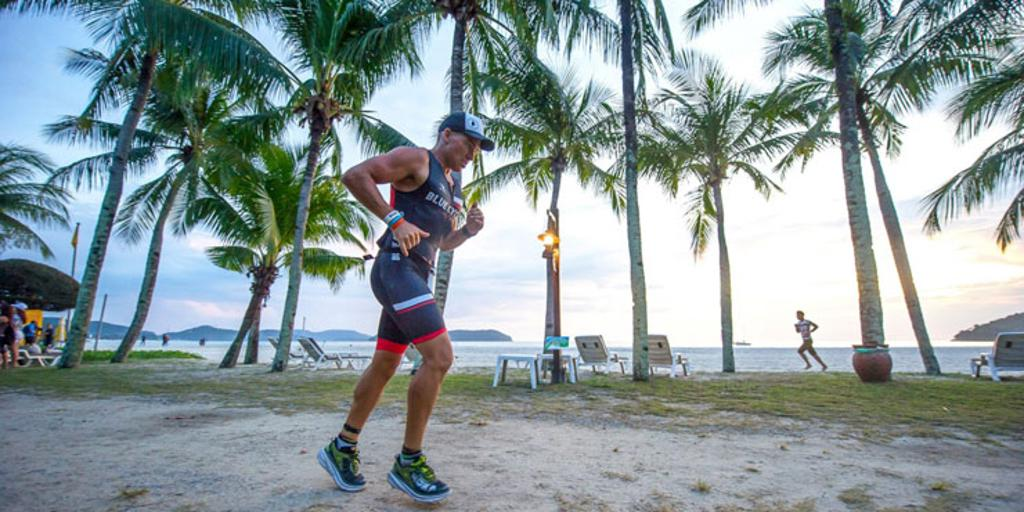 Triathlete running near palm trees and water at IM Malaysia