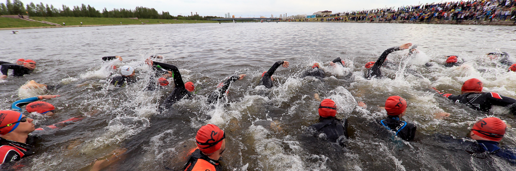 IRONMAN 70.3 Astana starting to swim in Ishim river with people watching and cheering them on from the right side of the river in Nur-Sultan