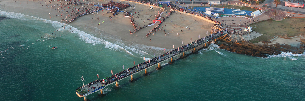 Scenic image from above of swim start at Hobie Beach at Nelson Mandela Bay / Port Elizabeth with athletes swimming or waiting to get into the sea and people watching at a pier