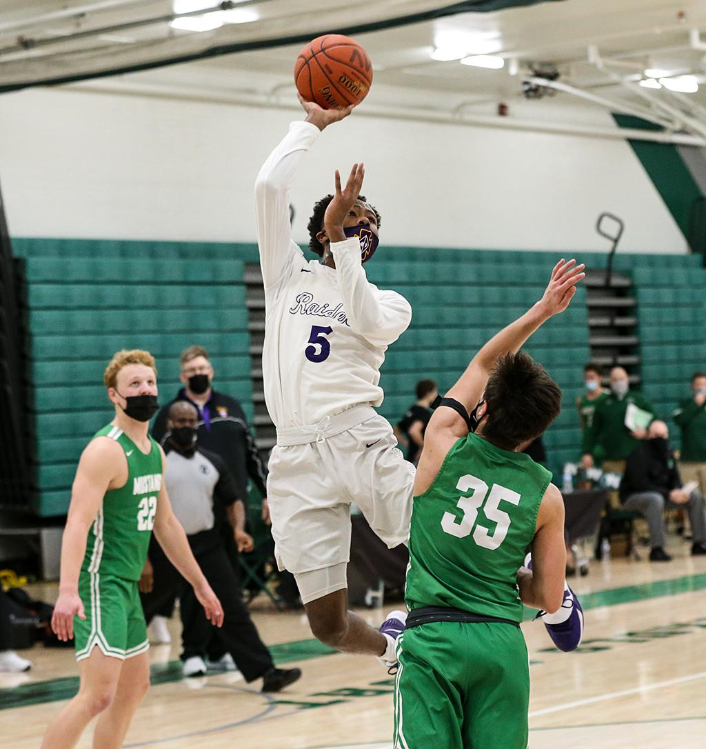 Junior Tre Holloman (5) drives the lane for a lay up late in the game. Holloman led the Raiders with 16 points and three rebounds on Friday night. Photo by Cheryl A. Myers, SportsEngine