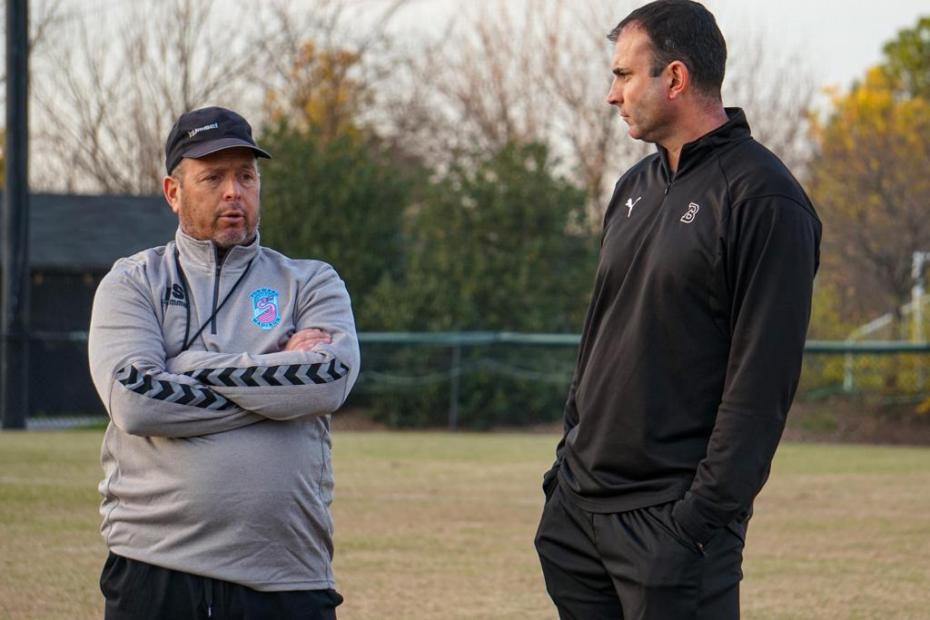 Daryl Shore chats with former teammate and current Birmingham-Southern head coach Greg Vinson during a Flamingos' training session this week. | Photo by Jason Klein