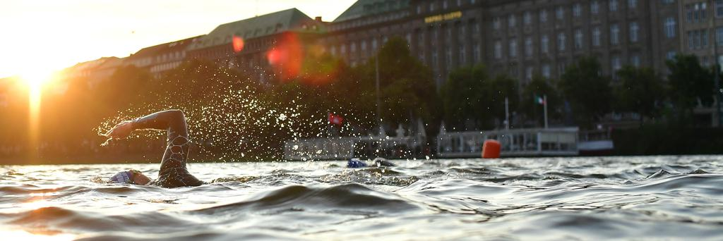 IRONMAN Hamburg athlete swimming through the Binnenalster and the Außenalster lake at sunrise