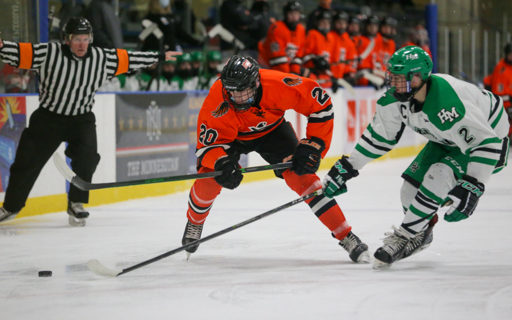 Grand Rapids' Hayden DeMars (20) carries the puck into the offensive zone as Hill-Murray's Joe Palodichuk (2) defends. The Thunderhawks beat the Pioneers 2-1 Saturday afternoon at Aldrich Arena in Maplewood.  Photo by Jeff Lawler, SportsEngine
