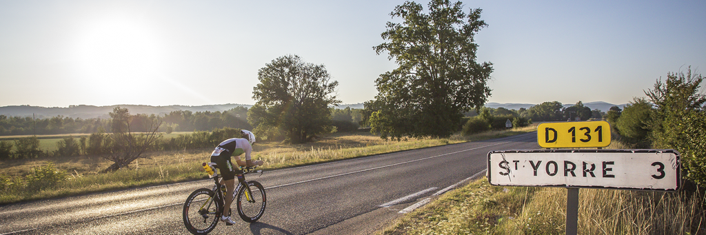 A single IRONMAN 70.3 Vichy athlete biking on his way to St. Yorre surrounded by fields and tree avenues