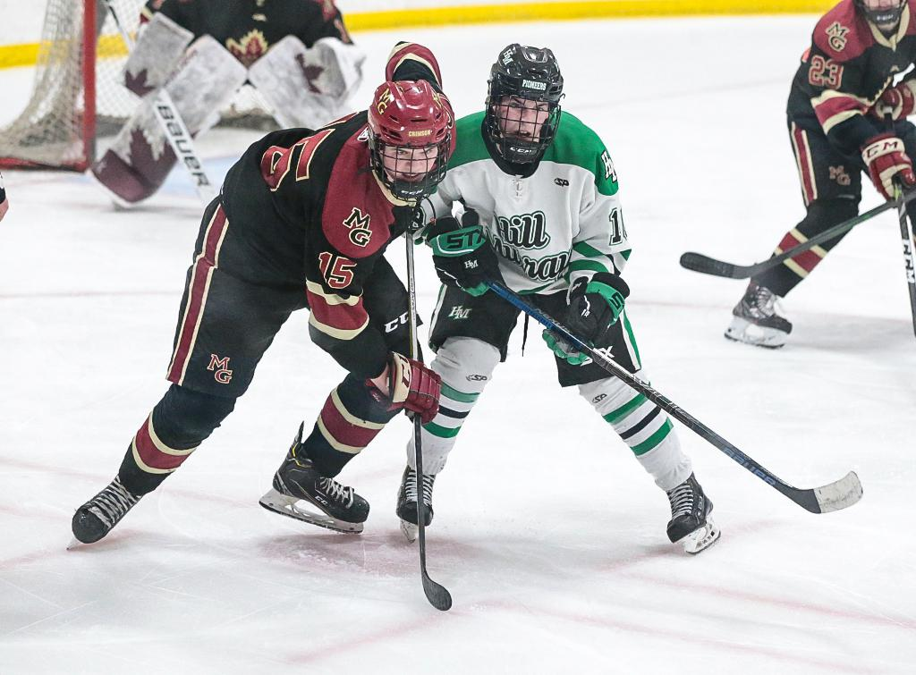 Maple Grove's Tyler Oakland (15) faces off against Nate Hardy (10). Oakland scored the Crimson's lone goal in the third period. Photo by Cheryl A. Myers, SportsEngine