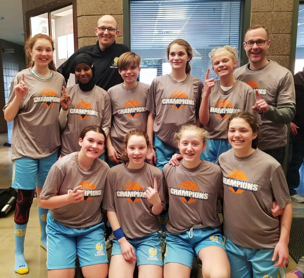 Minneapolis Lakers Girls 8th Grade Gold pose with their Championship t-shirts after taking 1st at the Eastview Girls Basketball Tournament in Apple Valley, MN
