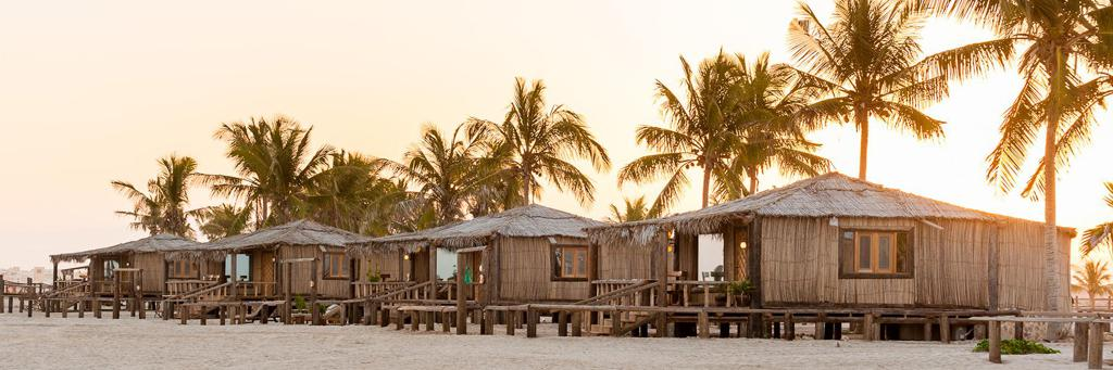 Beach of Salalah with many strand huts and palm trees at sunset in Oman