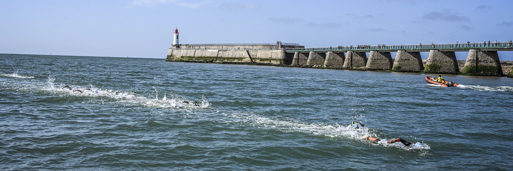 IRONMAN 70.3 Les Sables d'Olonne athletes swimming towards historic Vendée Globe canal next to a pier with a lighthouse