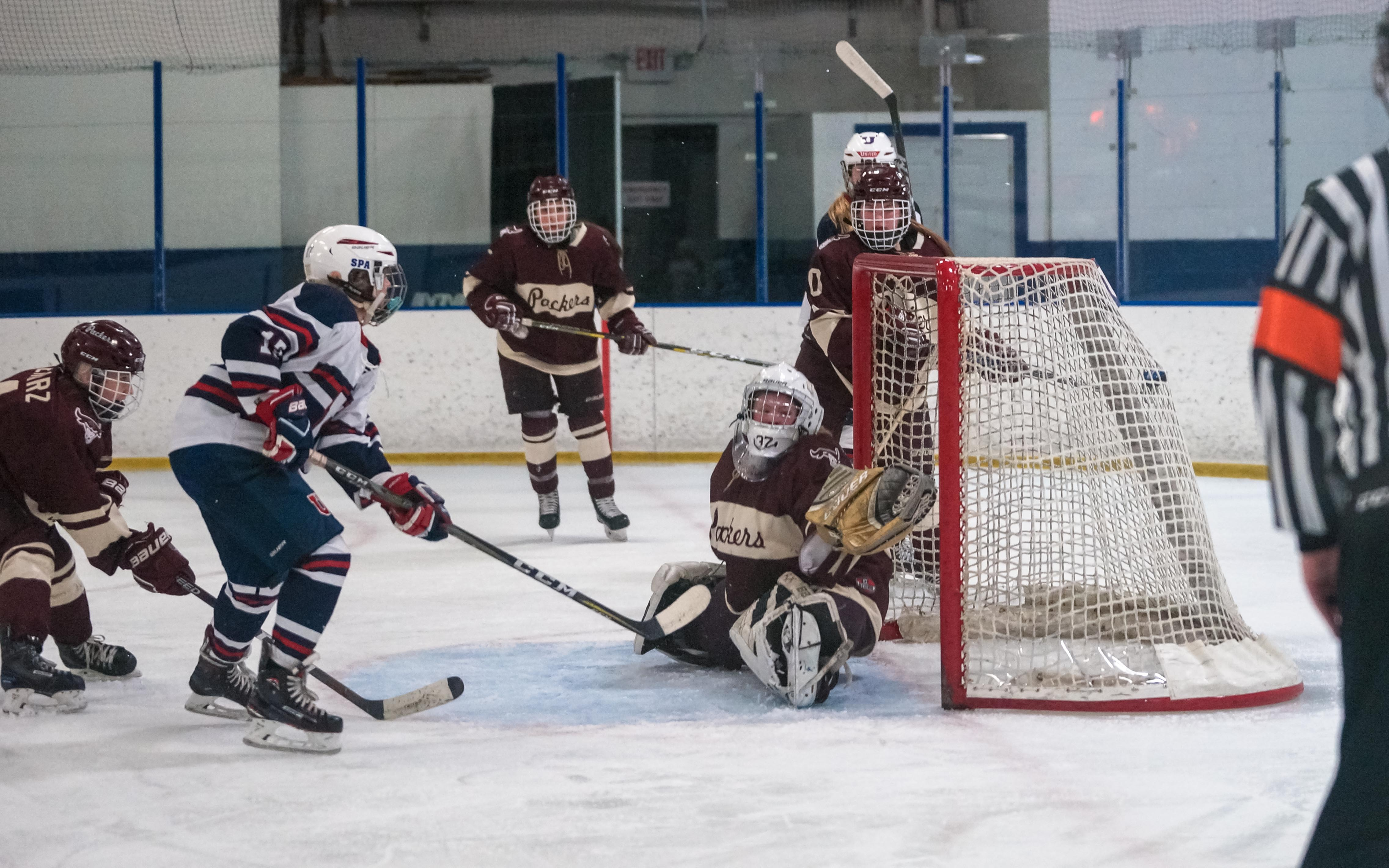 St.Paul United's Sammie Sabin (white) puts the eventual game-winner just over South St. Paul goalie Delaney Norman's shoulder Saturday. United added one more goal to beat the visiting Packers 5-3. Photo by Korey McDermott, SportsEngine