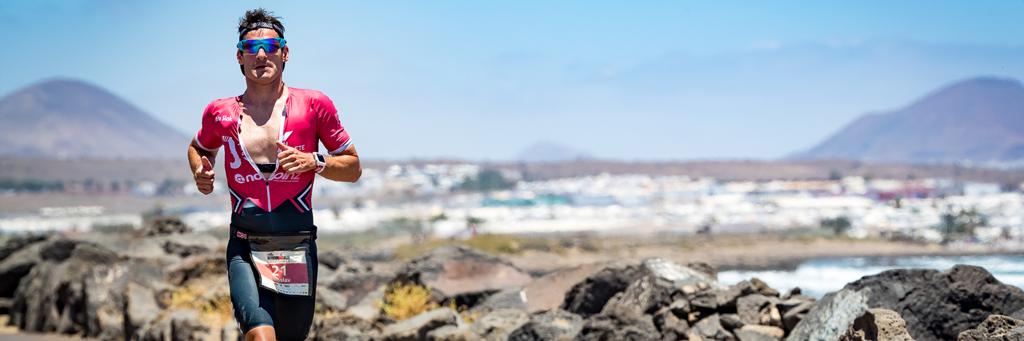 IRONMAN Lanzarote athlete running along Avenida de Las Playas during intense sunshine and beautiful views in the background