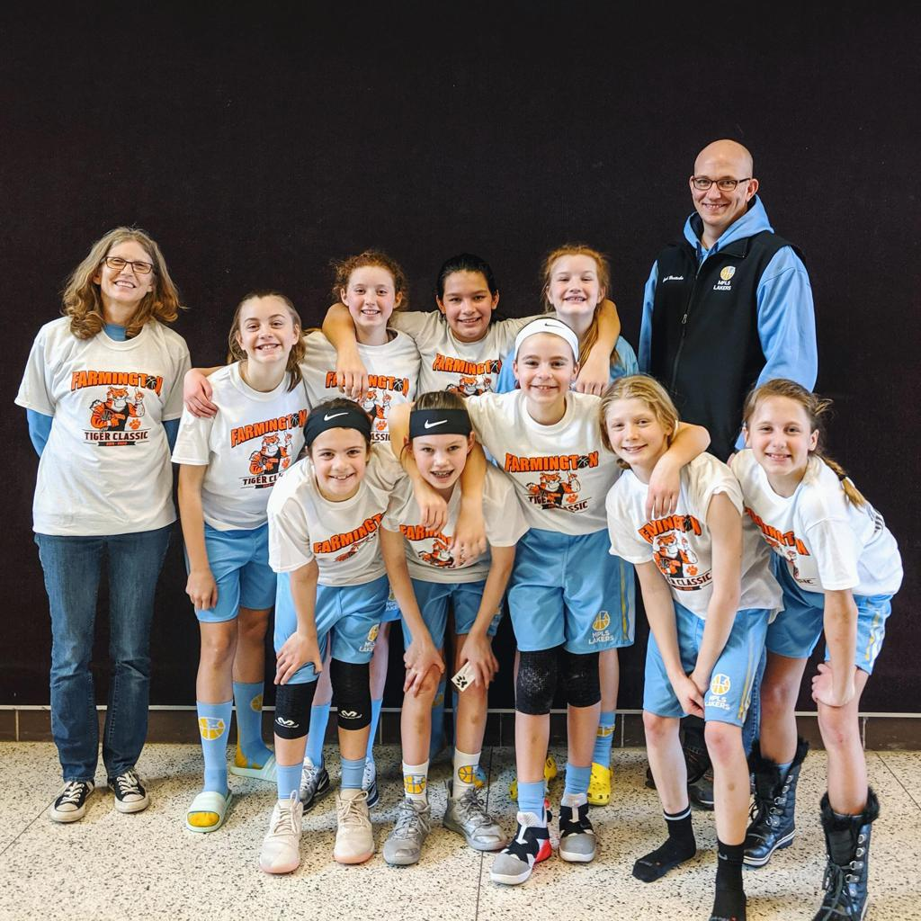 Mpls Lakers Youth Traveling Basketball Program Inc Girls 6th Grade Gold pose with T-Shirts after earning 3rd place at the Farmington Girls Tiger Classic tournament in Farmington , MN