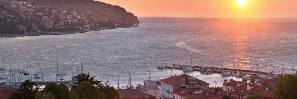Two opposite cities that are separated by the sea at sunset, which turns the sky and sea a little reddish in Slovenia