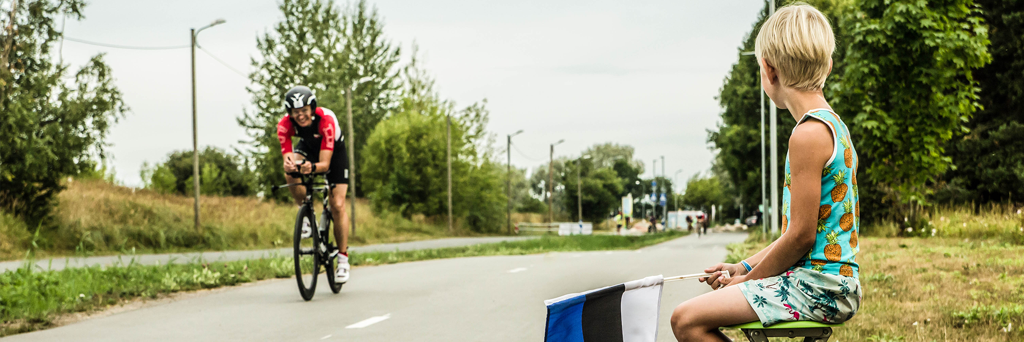Little boy waving with the Estonian flag while a smiling athlete is passing by on his bike