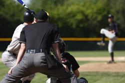 Umpire in black waiting to for pitcher to throw to batter with catcher