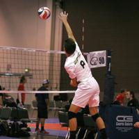 An Epic player hits the ball high above the net