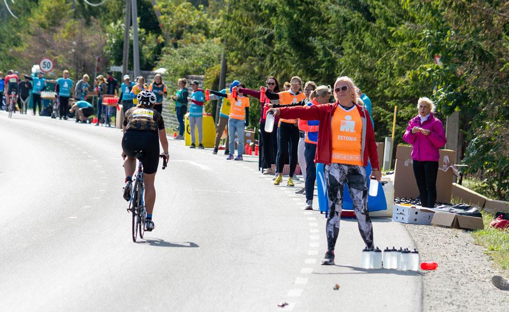 Volunteers handing water to athlete at IRONMAN Tallinn