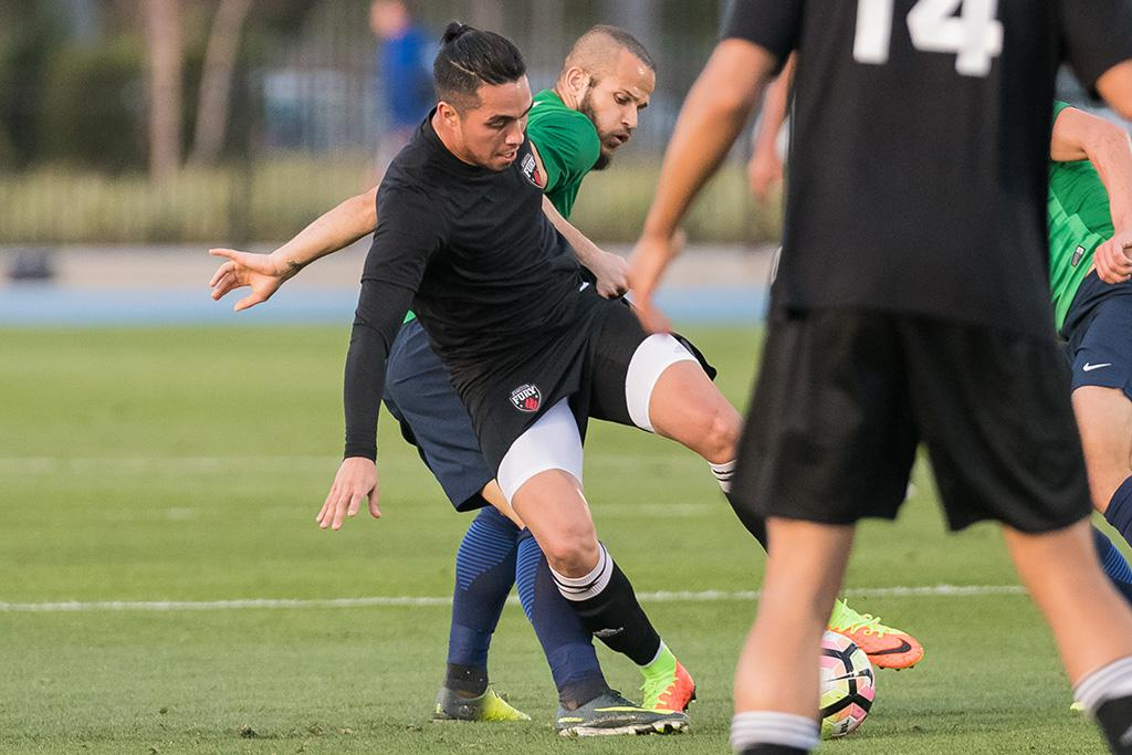 Gerardo Bruna, about to fall, fighting for possession against a player from Saint Louis FC