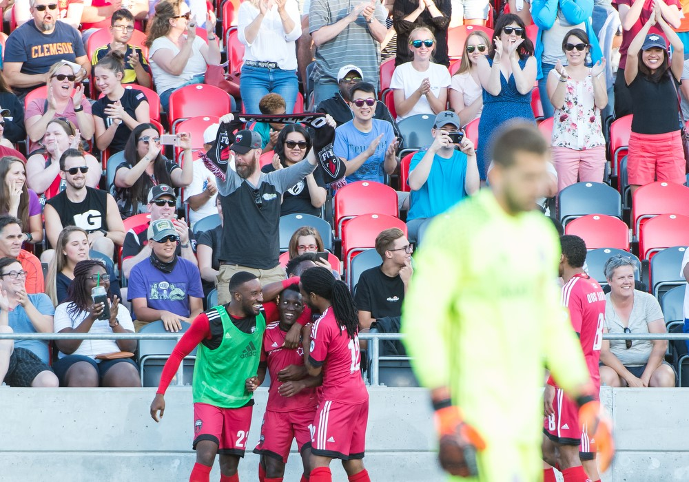 Azake Luboyera celebrating his goal with Jamar Dixon and Andrae Campbell in front of Fury FC Fans