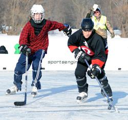 Team Lululemon's Krissy Wendell-Pohl, right, works the puck toward the goal on Saturday during the U.S. Pond Hockey Championships. Photo by Loren Nelson